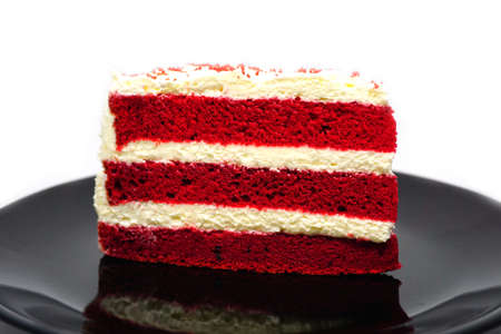 Cut cake Red velvet chocolate on black plate isolated on white background Banco de Imagens