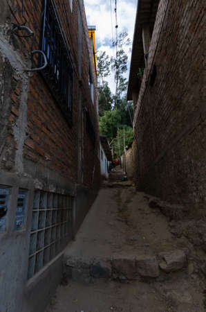poor alley with step in andean town of the sierra de peru with people in the background