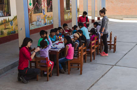 Yungay, Peru, August 4, 2014: Humble boys and girls around a table doing crafts with paint, paper, and glue accompanied by adults, horizontally Éditoriale