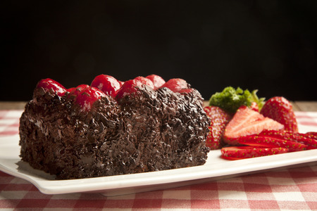 Piece of chocolate cake with icing and fresh berry photo
