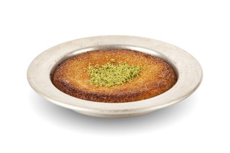 Turkish dessert kunefe with pistachio powder isolated white background
