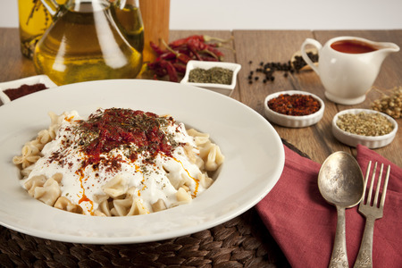 Turkish Manti manlama on plate with red pepper, tomatoes sauce, yogurt and mint