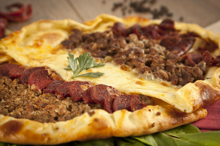 konya: Homemade traditional Turkish meal pizza pide stuffed with meat, cheese, pastirma and sausage
