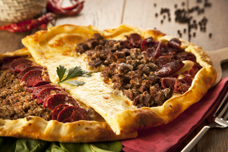 Homemade traditional Turkish meal pizza pide stuffed with meat, cheese, pastirma and sausage photo
