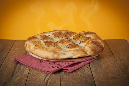 Turkish Ramadan Bread - Ramazan Pidesi on wooden table with yellow background