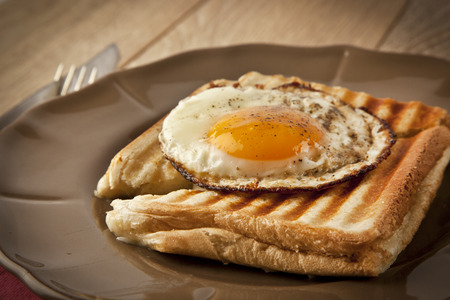 Scrambled eggs with toast on brown plate wooden table photo