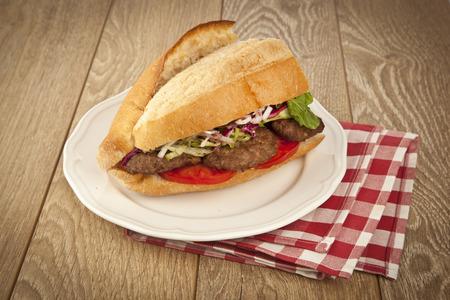 Delicious Turkish Kofte Sandwich (meatballs) wooden background photo