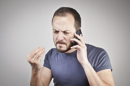 angry: angry young man while answering smart phone not understood Stock Photo