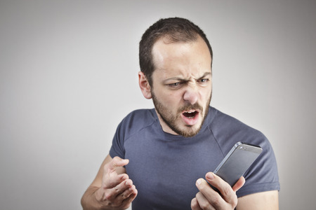 understood: angry young man while answering smart phone not understood Stock Photo