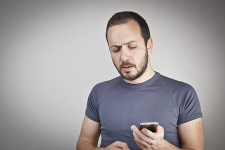 young man gesturing while answering smart phone not understood photo