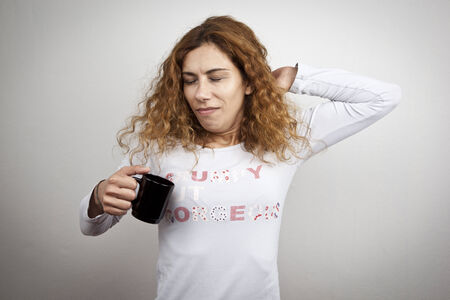 Tired sleepy woman waking up with cup of coffee photo