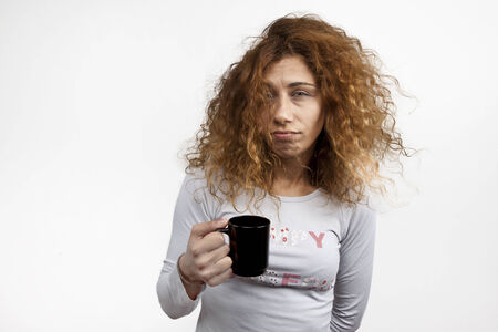 Tired sleepy woman waking up with cup of coffee