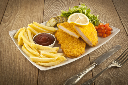 Fried Schnitzel Chicken and pork chop French fries and vegetables