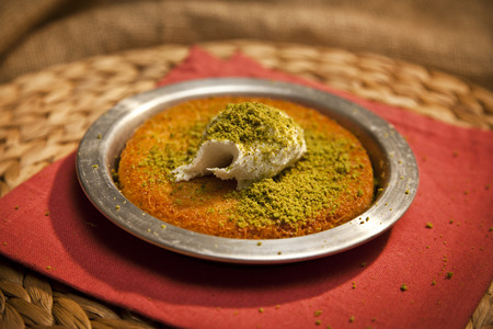 Delicious traditional Turkish kunefe with pistachio on it. Served hot and with syrup