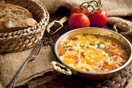 Menemen Turkish breakfast food egg, tomatoes and pepper in pan with concept background Imagens