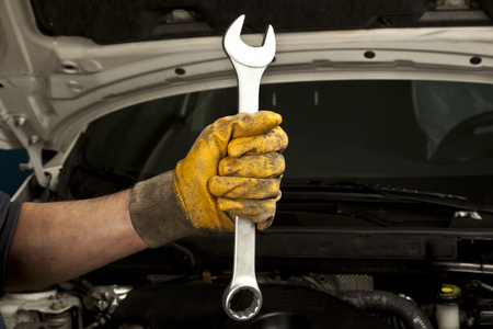 Hand holding a wrench Imagens