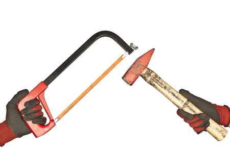 Two hand hold hammer and hacksaw on a white background