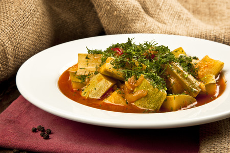 zucchini vegetable casserole with dill weed in a plate on table Imagens