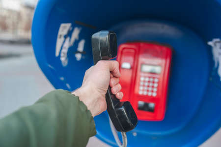 the handset of the pay phone in the hand