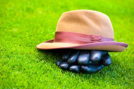 retro mans hat autumn garden gloves green grass Stockfoto
