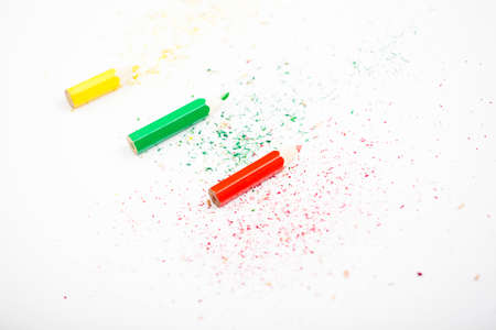 Three small pencil red green yellow white background