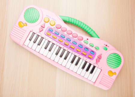 plastic pink toy piano wooden table