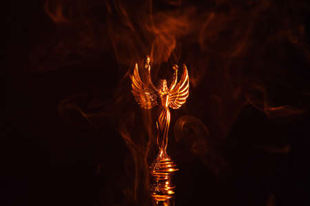 gold angel statue smoke dark background