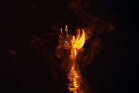 gold angel statue smoke dark background