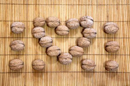 walnut heart symbol wooden background Stock Photo