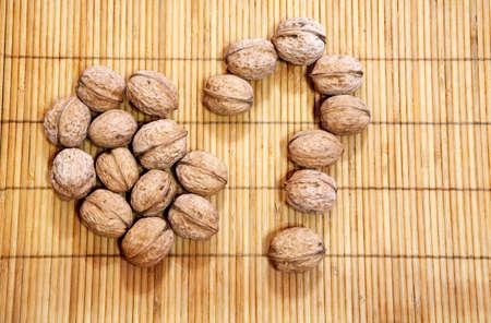walnut question mark wooden background Stock Photo