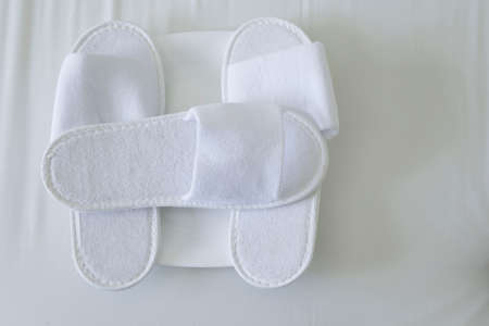 hotel bed with white slipper background Stock Photo