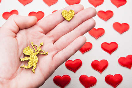 gold cupid heart hand leather background Foto de archivo