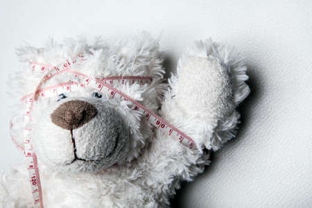 image of toy bear with meter tape on white background Stock fotó