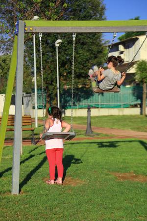 obesidad infantil: Dos chicas en el patio de recreo. Una niña con un problema de peso no puede subir en un tambaleo.