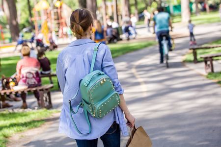 Young girl walking through a city park with a mint-color backpack, in the middle of the roadway, holding a paper bag in a hand.Back view, horizontal. Stock Photo