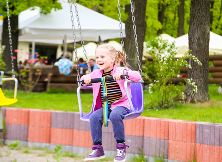 chain swing ride: A cute young girl riding a chain carousel swing.