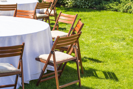 round chairs: Round table covered with white cloth and chairs stand on a green lawn outdoors. Stock Photo