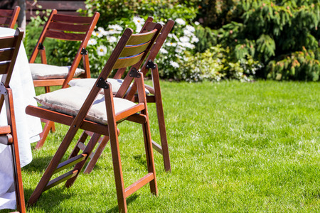 Round table covered with white cloth and chairs stand on a green lawn outdoors. Stock Photo
