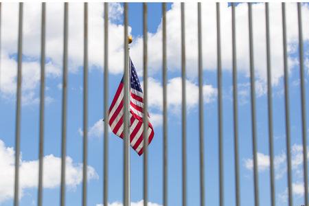 The USA flag visible through fence grates Stock Photo