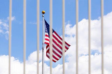 The USA flag visible through fence grates Standard-Bild