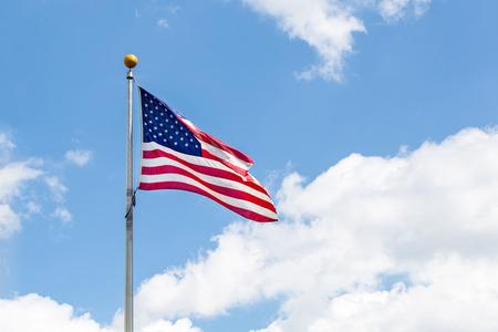 The american Flag waving over blue sky Standard-Bild