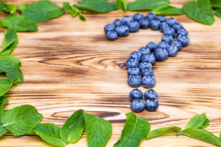 Question sign made of fresh ripe natural blueberries with bright green spearmint frame on a brushed wooden background. Healthy diet  question concept Stock Photo
