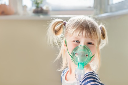 Happy smiling kid using nebuliser mask. Inhalation therapy curing chest cold and coughing. Healthcare and disease prevention concept Stock Photo