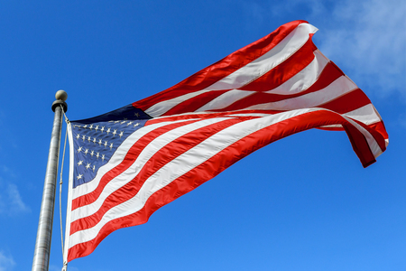 USA flag waving against clear blue sky on bright sunny day