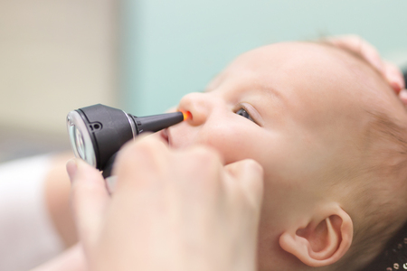 Infant in pediatric clinic. Close-up doctors hand with modern otoscope examining babys nose. Children healthcare and disease prevention.
