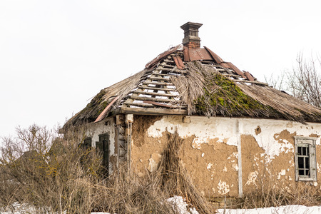 Old abandoned house. Weathered ruined building with broken straw roof. Aged rural home made ofrocks,  stone and clay.