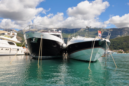 Luxury yacts moored at marina. Beautiful scenic bay. Bright sunny day with blue sky and mountains on the background. Boat trips and yacht for rent. Front  view.