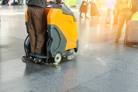 Man driving professional floor cleaning machine at airport or railway station.  Floor care and cleaning service agency.  Archivio Fotografico