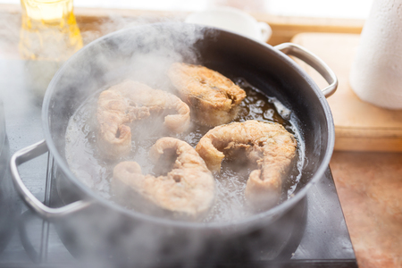Pan with frying sturgeon fish. Outdoor kitchen. Summer barbeque and vacation.