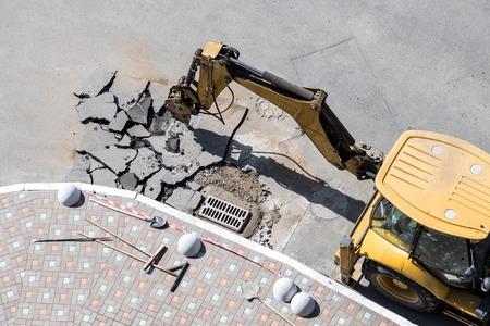 Big jackhammer drill drilling road.Heavy machinery crushing asphalt for stormwater drain repair.